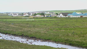 The new school site, with the Barvas Hall, football pitch, and the current Barvas School in the background, and Abhainn Bharabhais in the foreground