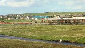 The new school next to Abhainn Bharabhas, with the old school at Heatherhill seen in the background. The old school was established in the 1870s, and thus its closure is a significant point in the history of Barvas and Brue