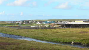 The new school site, with Abhainn Bharabhais in the foreground, and the old Barvas School seen in the distance behind