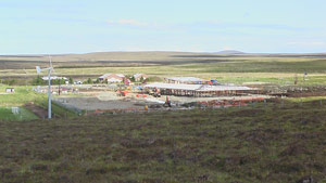 Work proceeding on the new school in Barvas, with the Barvas Moor and the Muirneag seen in the background. On the left of the photo is a windmill for generating electricity
